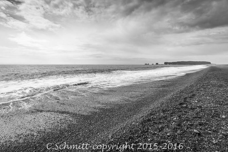 La plage de Reynisfjara en Islande et Dyholaey sous le ciel noir photo noir et blanc