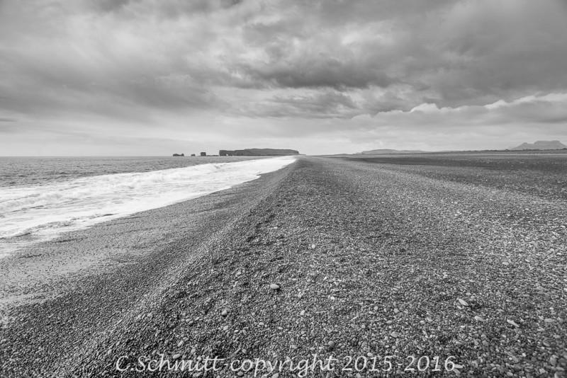 La plage de galets noirs de Reynisfjara en Islande et Dyholaey sous le ciel noir photo noir et blanc