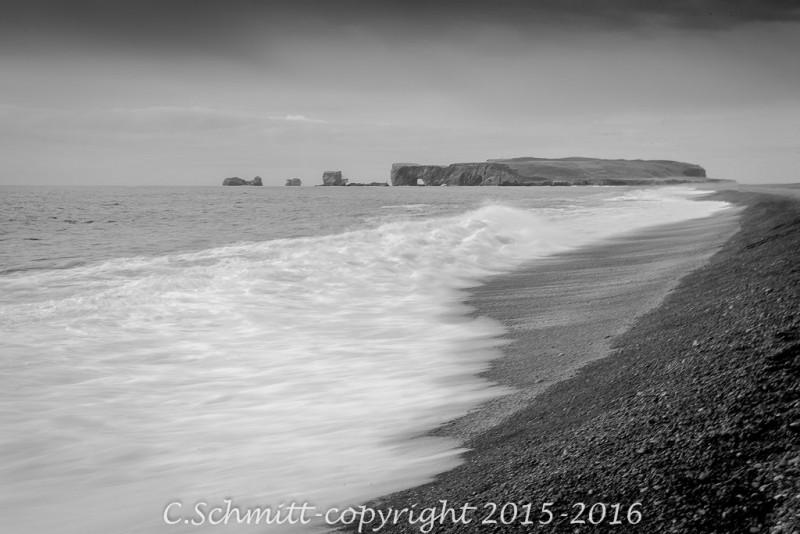 Vue sur le promontoire de Dyrholaey depuis la plage de Reynisfjara en Islande photo noir et blanc