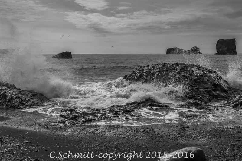 Vague éclatant sur les rochers d'une crique à Dyrholaey en Islande en photo noir et blanc